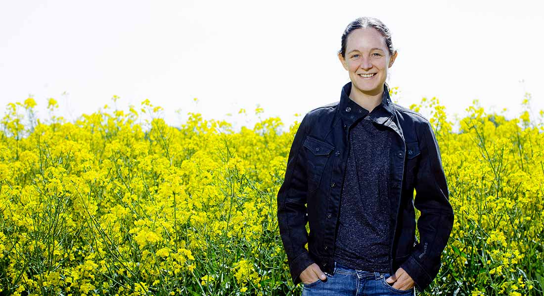 Picture of Professor Marianne Nissen Lund with rapeseed field as background